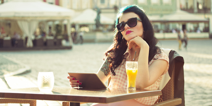 Young woman using a digital tablet in the outdoor restaurant